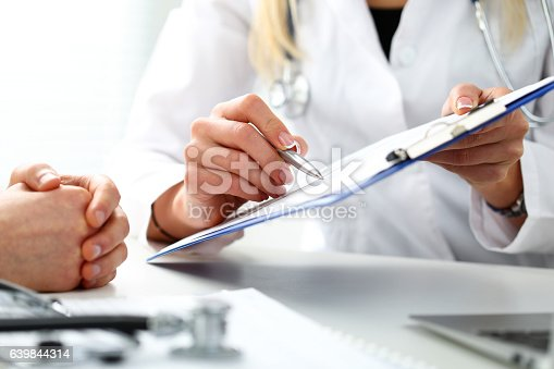 istock Female doctor hand hold silver pen filling patient history list 639844314