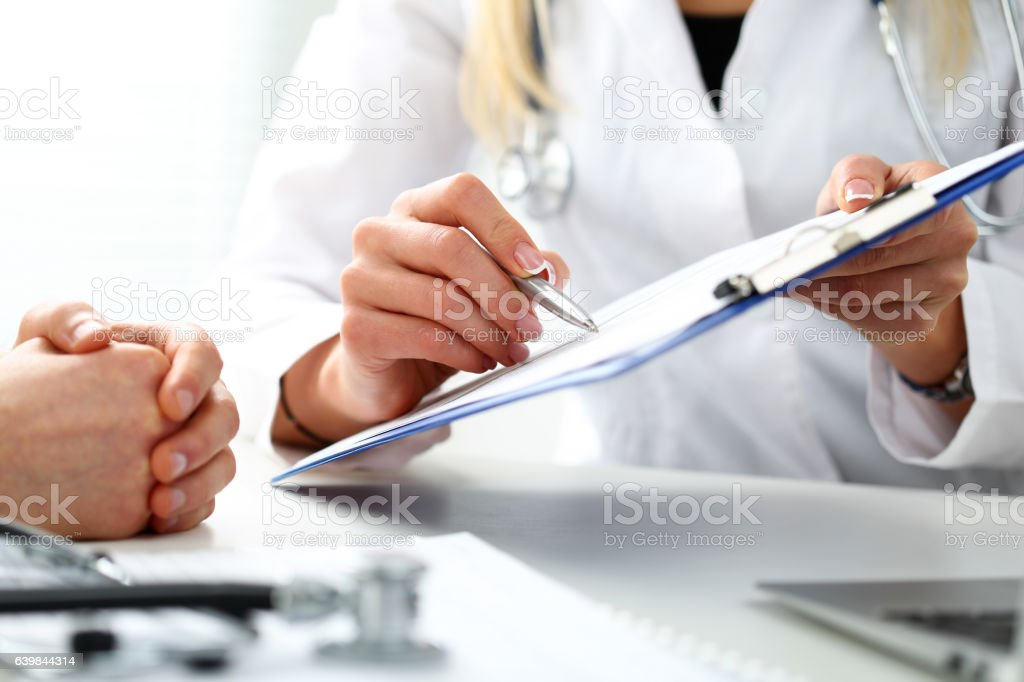 Female doctor hand hold silver pen filling patient history list - foto de stock
