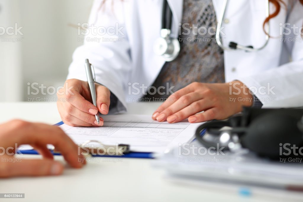 Female doctor hand hold silver pen filling patient history list stock photo