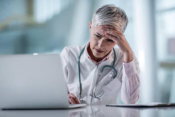 Ärztin mit einem Kopfschmerz, während Sie sich in Arzt-Büro. – Foto