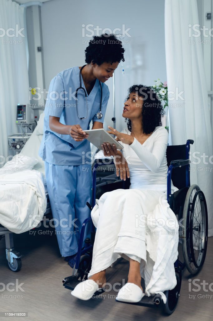 Female doctor helping disabled female patient to use digital tablet in the ward Side view of African-American female doctor helping disabled female patient to use digital tablet in the ward at hospital A Helping Hand Stock Photo