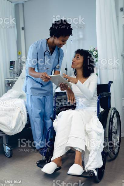 Female Doctor Helping Disabled Female Patient To Use Digital Tablet In The Ward Stock Photo - Download Image Now