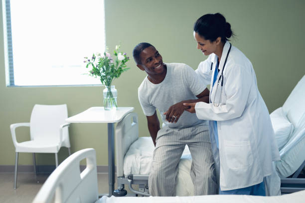 Female doctor helping male patient to get up on hospital bed in the ward stock photo