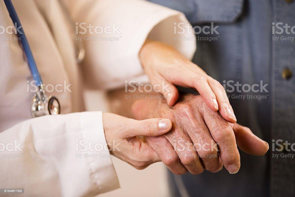 Doctora ayuda hombre senior paciente.  Sosteniendo su mano. - foto de stock