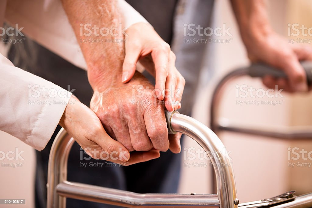 Female doctor helps senior man patient use walker. Holding hands. stock photo