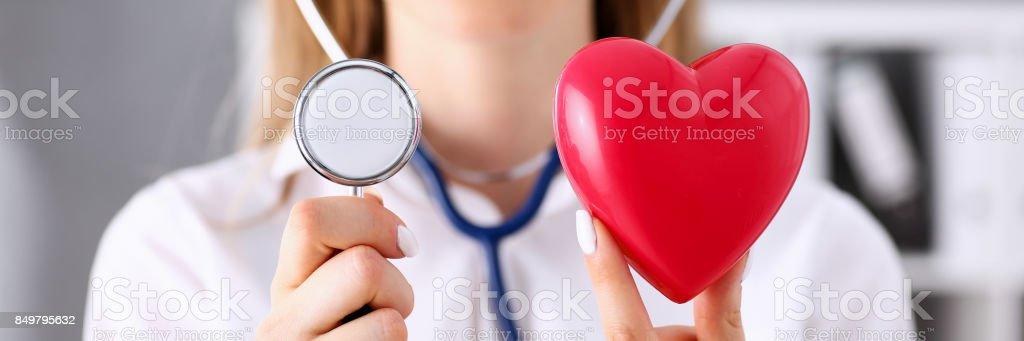 Doctora sostenga en brazos rojo corazón y fonendo - foto de stock
