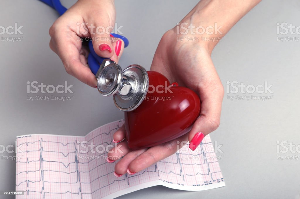 Female doctor hold in hands red toy heart and stethoscope. Cardio therapeutist, arrhythmia concept stock photo