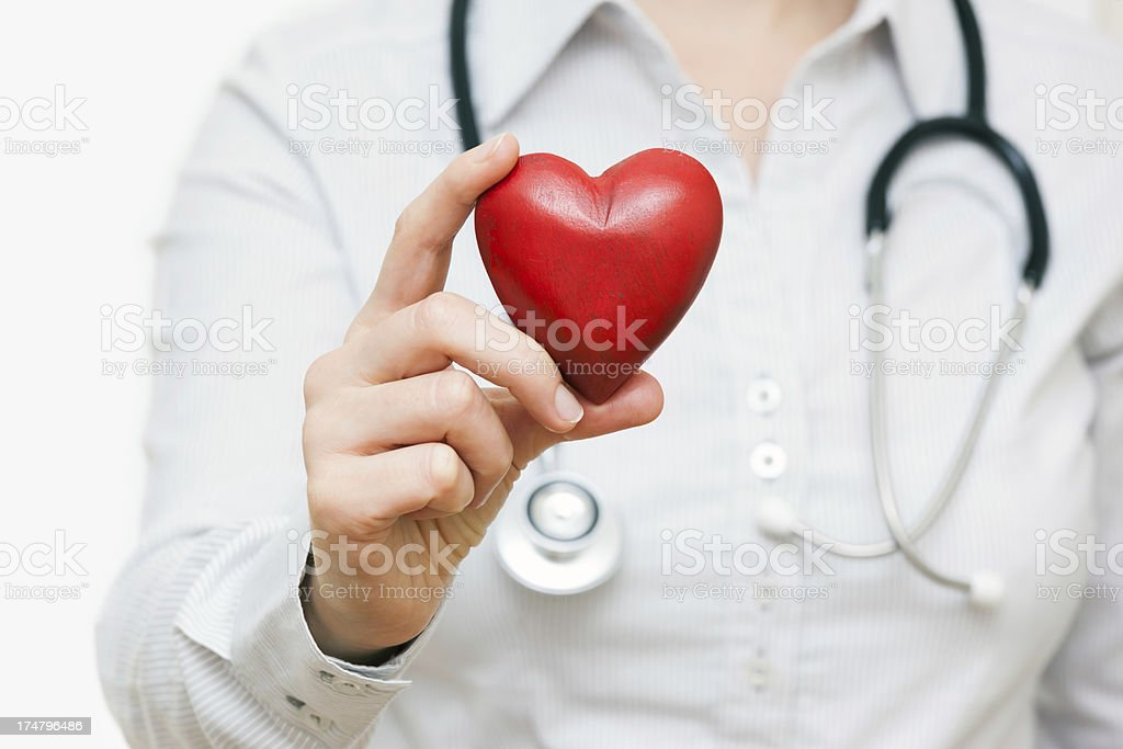 A female doctor holding a wooden carved heart royalty-free stock photo