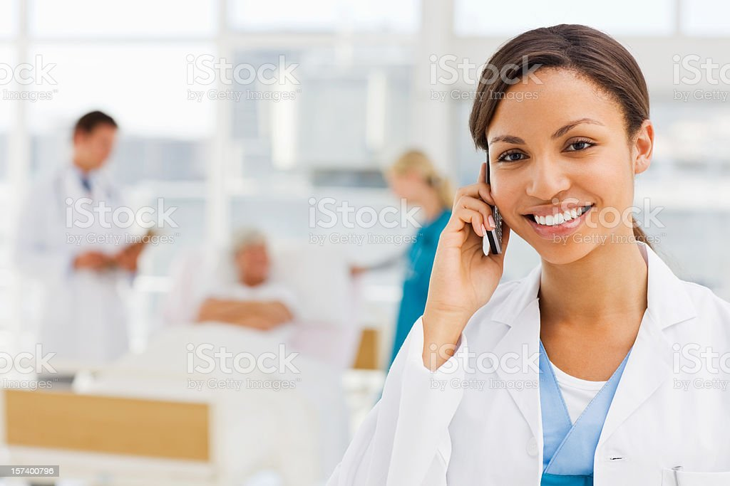 Female doctor holding cellphone with colleagues and patient in background royalty-free stock photo