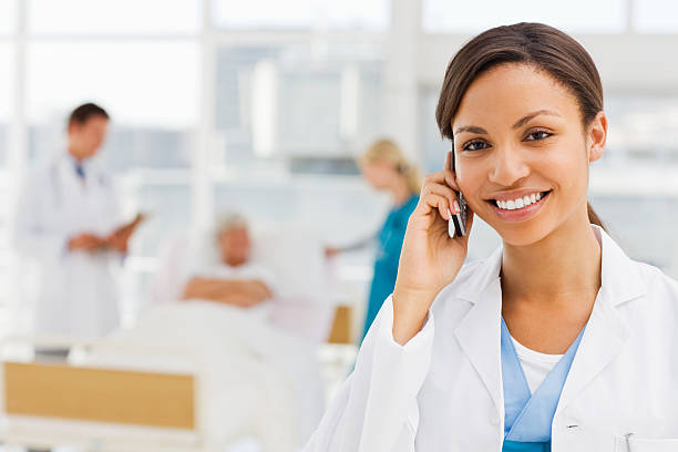 female doctor holding cellphone with colleagues and patient in background - nurse on phone stock photos and pictures