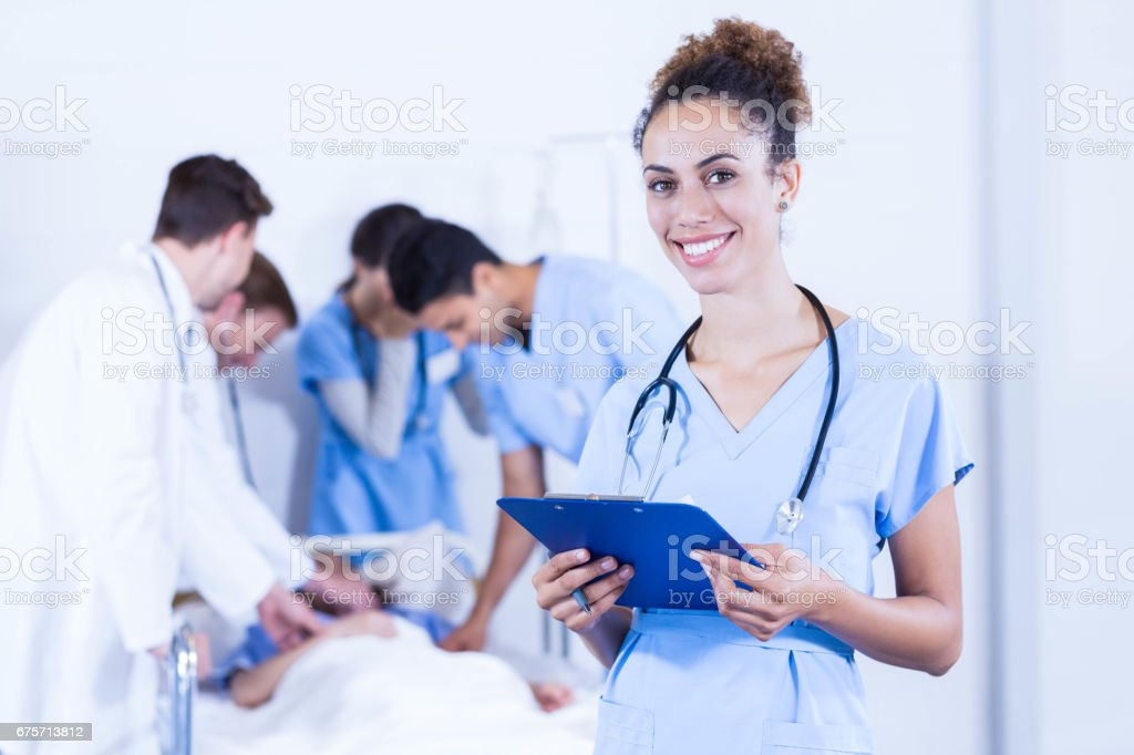 Female doctor holding clipboard and smiling at camera royalty-free stock photo