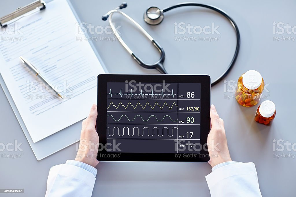 POV Female doctor holding digital tablet with heart monitor stock photo