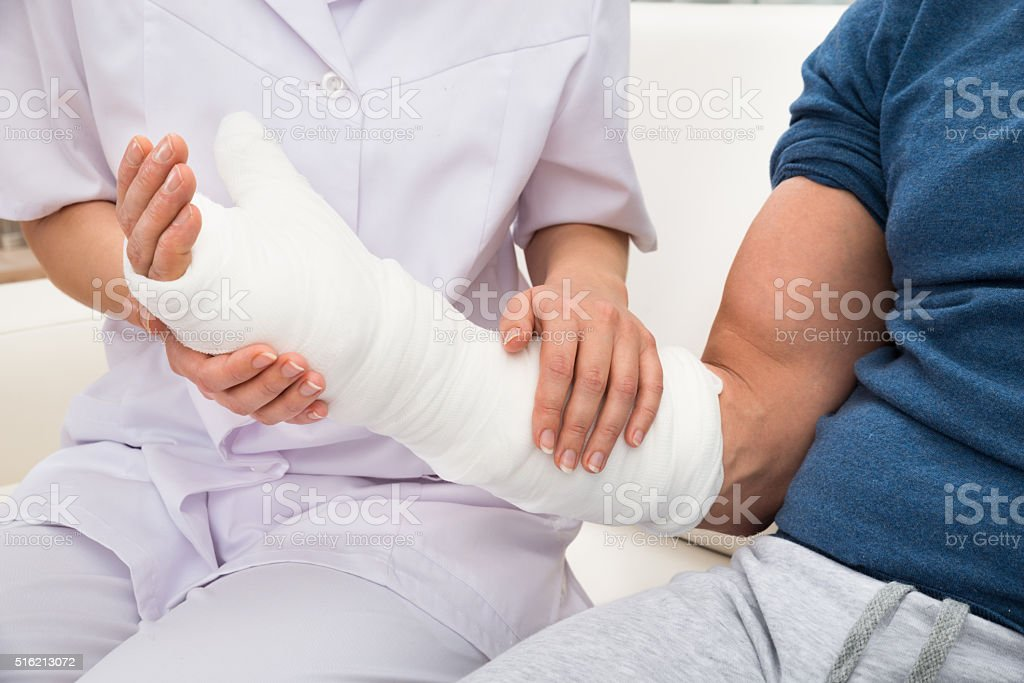 Mujer médico sostiene dañadas mano de un paciente - foto de stock