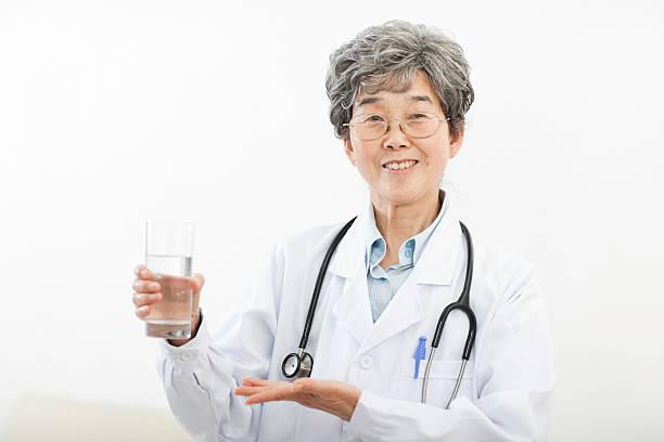 ärztin hält glas wasser, lächeln, porträt - leitungswasser trinken stock-fotos und bilder