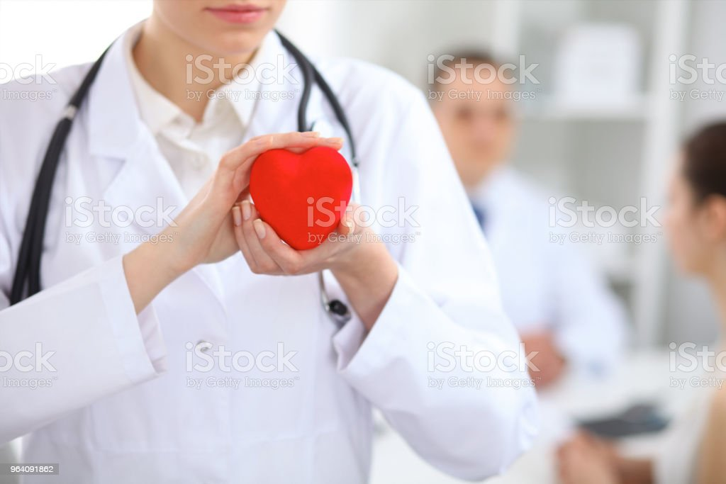 Female doctor holding heart in her hands.  Doctor and patient sitting in the background. Cardiology in medicine and health car - Royalty-free Adult Stock Photo