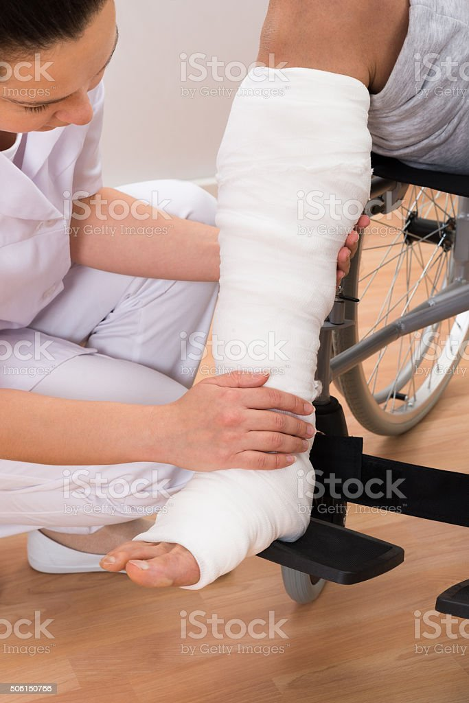 Female Doctor Holding Patient's Leg stock photo