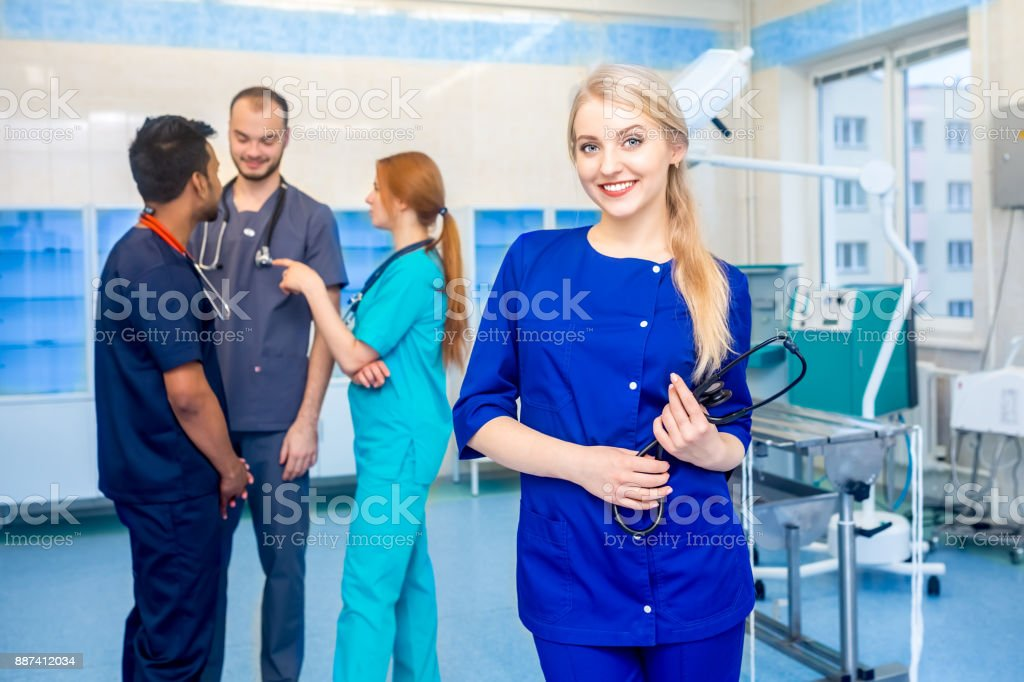 Female doctor in front of team, looking at camera and smiling with medical team in background. Multiracial team of young doctors in a hospital standing in a operating room stock photo