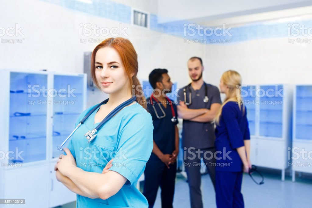 Female doctor in front of team, looking at camera with medical team in background. Multiracial team of young doctors in a hospital standing in a operating room stock photo