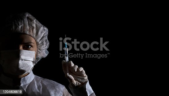 Female doctor (or nurse) in protection face mask, medical cap and glove holds syringe with vaccine in her hand on black background. Half face in shadow, dramatic emotion. Concept of virus protection, prevention of epidemics, treatment of diseases. Banner, copy space