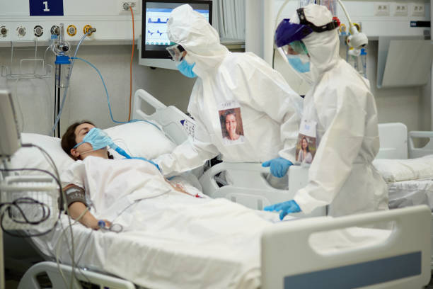 Female Doctor in Protective Suit Checking COVID-19 Patient stock photo