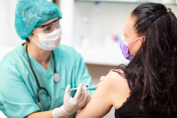 Female doctor in protective workwear injecting vaccine and monitoring patient stock photo