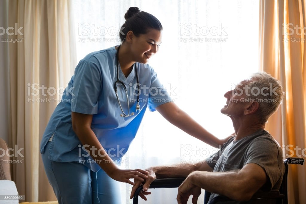 Female doctor interacting with senior man in nursing home stock photo