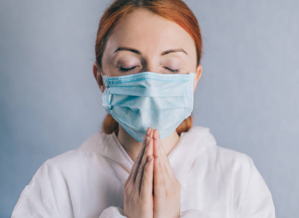 A female doctor is praying. Close up. stock photo