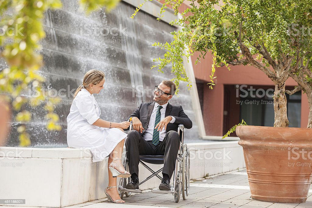 Female Doctor is talking to businessman on wheelchair stock photo