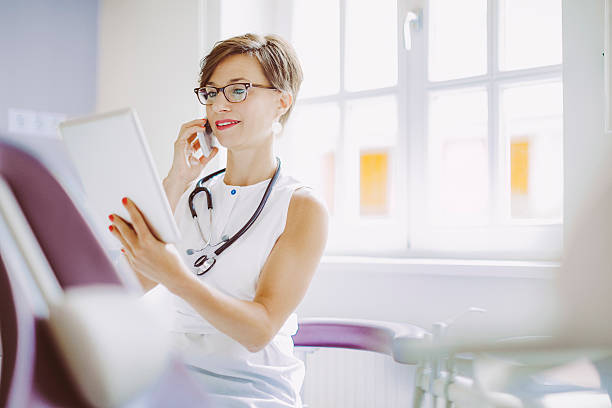 female doctor is working in the surgery - nurse on phone stock photos and pictures