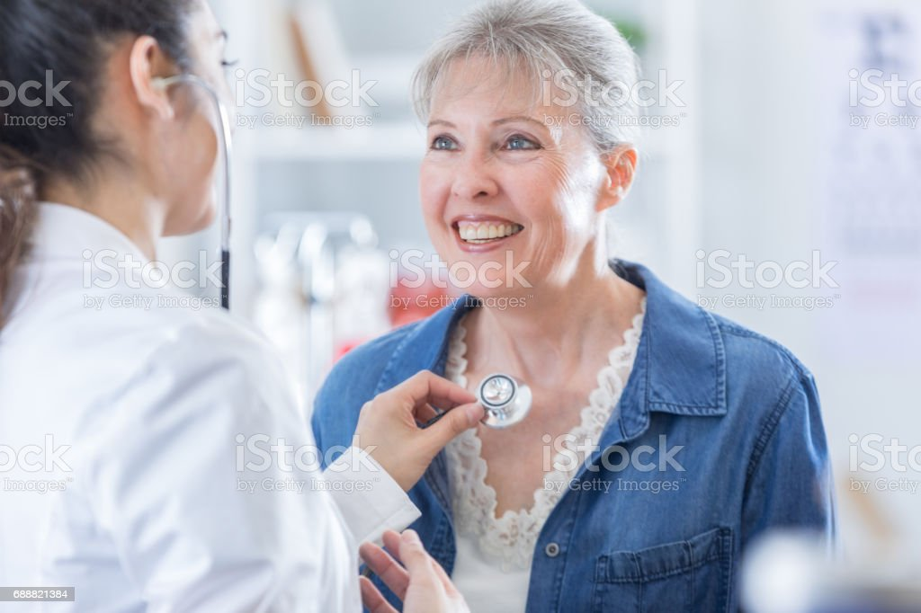 Female doctor listens to senior woman's heartbeat stock photo