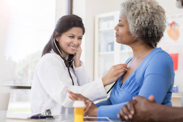 Female doctor listens to senior woman's lungs stock photo