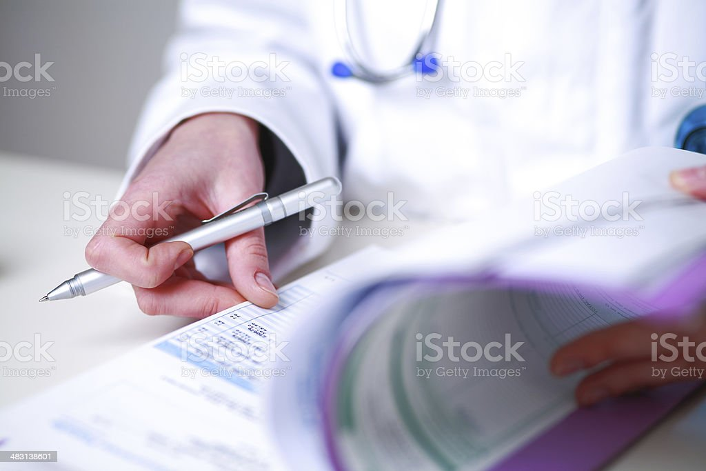 female doctor looking a medical file stock photo