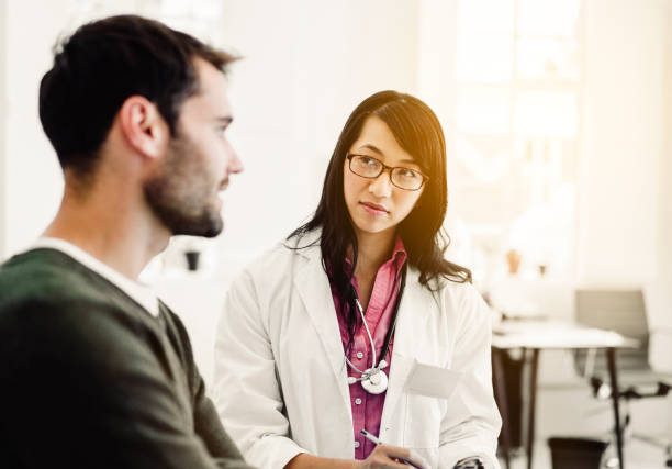 Female doctor looking at male patient in clinic stock photo