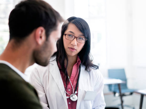 female doctor looking at male patient in clinic - doctor visit stock photos and pictures