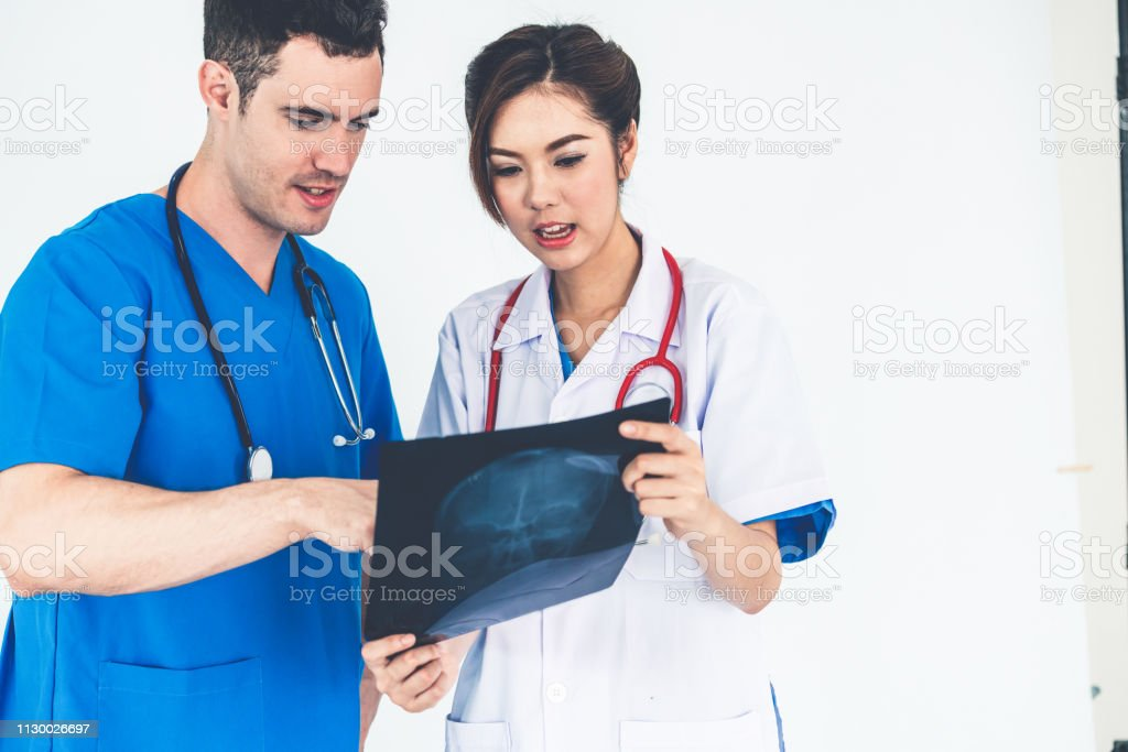Female doctor looking at x ray film of patient head injury while...