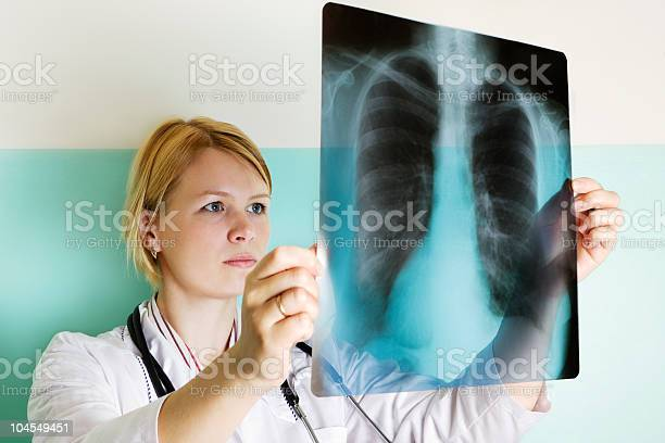 Female Doctor Looking At Xray Stock Photo - Download Image Now