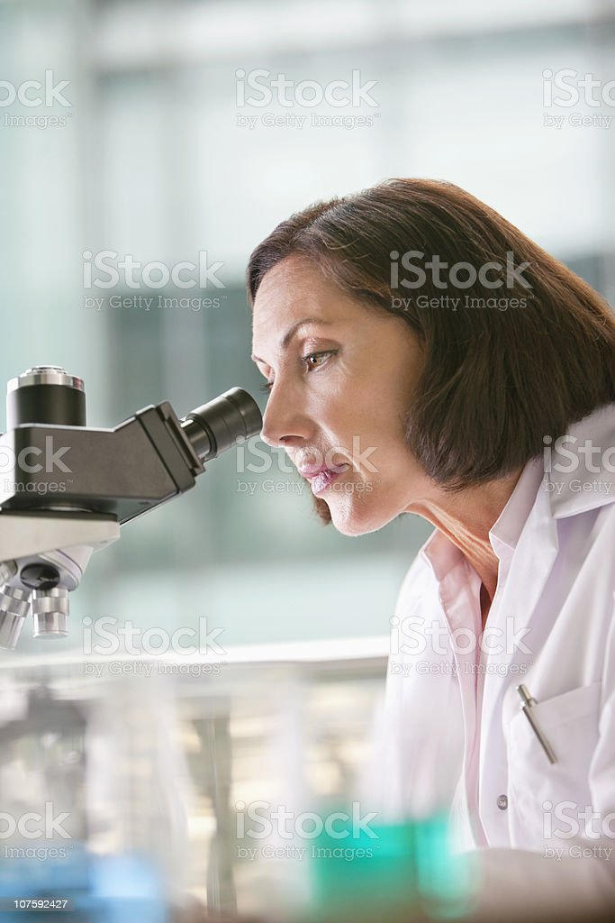 Female doctor looking through a microscope in a laboratory royalty-free stock photo
