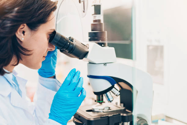 Female doctor looking through a microscope stock photo