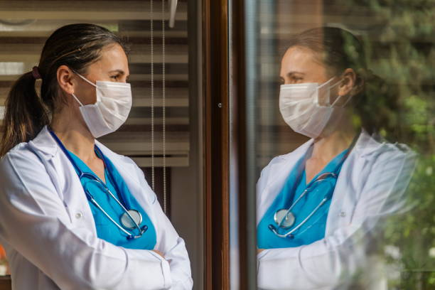 Female doctor looking through window at hospital stock photo