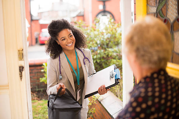 female doctor makes a house call to senior A happy looking female general practitioner doctor enters the house of a senior lady. We look over the shoulder of the senior lady as she opens the door and the female doctor enters. She is carrying a medical bag , clipboard and folder case , and is wearing a stethoscope over a trouser suit and id badge lanyard. outpatient stock pictures, royalty-free photos & images
