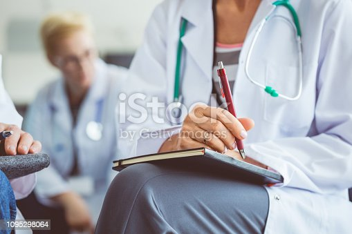 Close up of female medical professional making notes during seminar. Doctor writing notes in diary during healthcare conference.