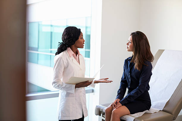 Female Doctor Meeting With Patient In Exam Room stock photo
