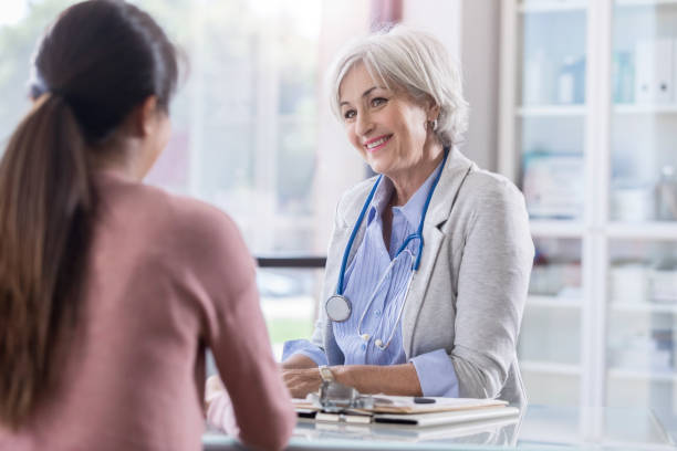 female doctor meets with female patient - gynecologist stock pictures, royalty-free photos & images