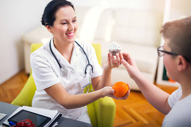 Female doctor nutritionist and teenager patient stock photo