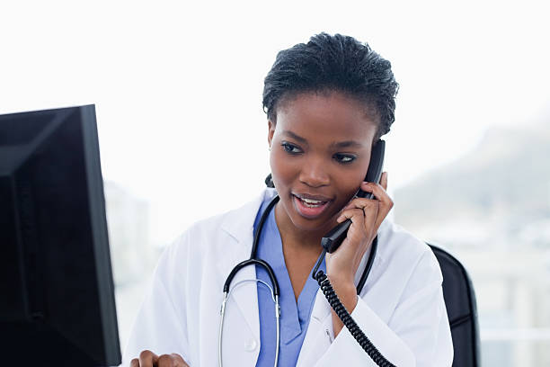 female doctor on the phone while using a computer - nurse on phone stock photos and pictures