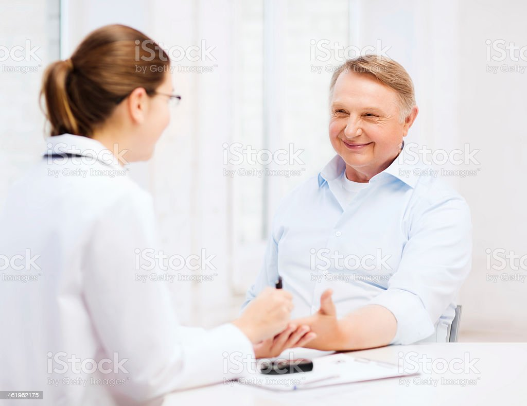 female doctor or nurse measuring blood sugar value stock photo