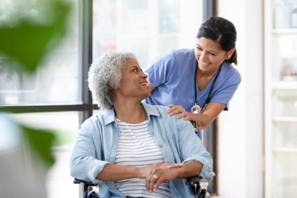 Female doctor pauses to encourage senior woman in wheelchair stock photo
