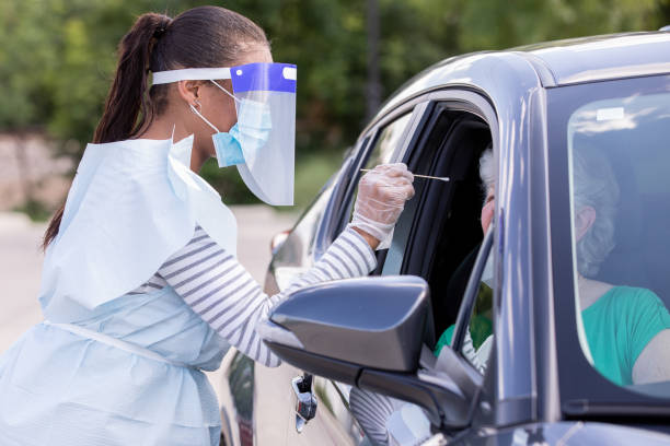 Female doctor performing Covid-19 tests while patients sit in cars stock photo