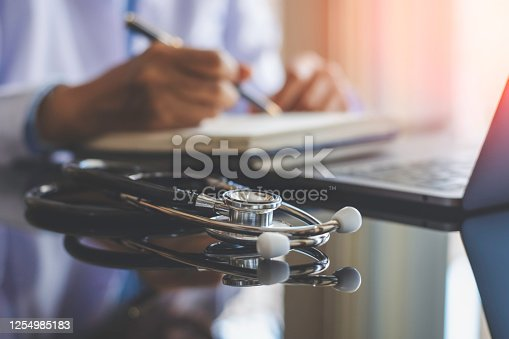 Closeup female doctor work on laptop computer and writing note on white empty notebook at office in clinic or hospital. Online medical, education , ehealth concept.