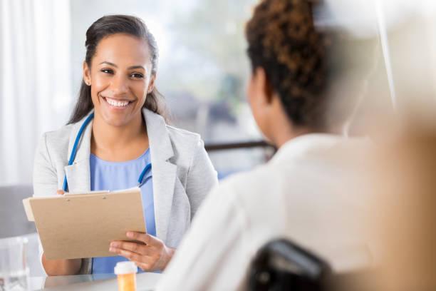 女医は車椅子患者に薬を処方します。 ストックフォト